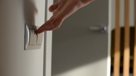 toggle : Male hand turning on. Close-up shot. Door on Background