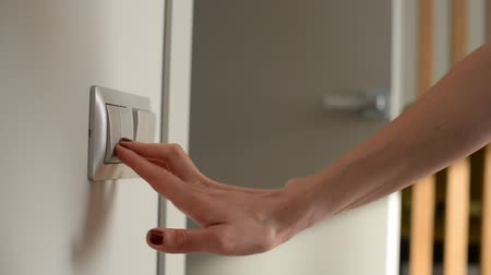 press wall : Female hand turning off the light switch. Close-up shot. Door on Background