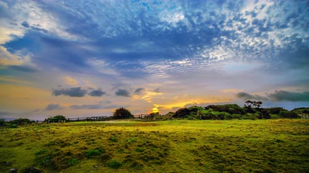 okinawa : Timelapse shot of sunrising in cape Manzamo area, golden to blue sky and beautiful cloud passby as background. Okinawa, Japan, April 2018.