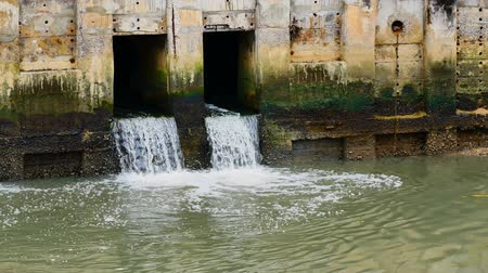 culvert : Daily life video After the rain. Water from a canal in the city is dropping down to the sea. To drain water and to prevent flooding in the city in flooding concept Stock Footage