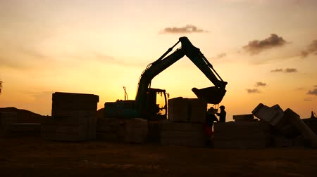 гидравлический : Construction Video At construction site The silhouette excavator is digging ground and lifting a large mortar with engineering and construction workers to help with colorful sunset Стоковые видеозаписи