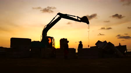 cova : Construction Video At construction site The silhouette excavator is digging ground and lifting a large mortar with engineering and construction workers to help with colorful sunset Stock Footage