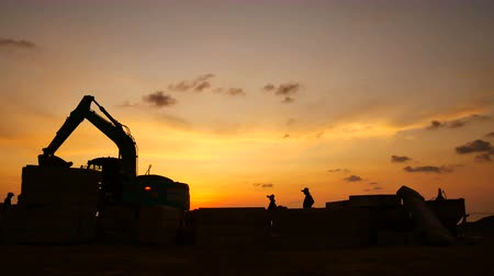 hydraulic : Construction Video At construction site The silhouette excavator is digging ground and lifting a large mortar with engineering and construction workers to help with colorful sunset Stock Footage