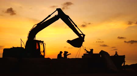 backhoe loader : Construction Video At construction site The silhouette excavator is digging ground and lifting a large mortar with engineering and construction workers to help with colorful sunset Stock Footage
