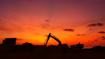 hydraulické : Construction Video At construction site The silhouette excavator is digging ground and lifting a large mortar with engineering and construction workers to help with colorful sunset Dostupné videozáznamy