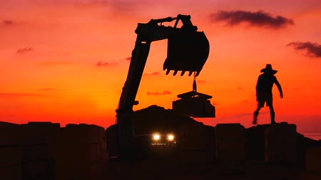 buldozer : Construction Video At construction site The silhouette excavator is digging ground and lifting a large mortar with engineering and construction workers to help with colorful sunset Stok Video