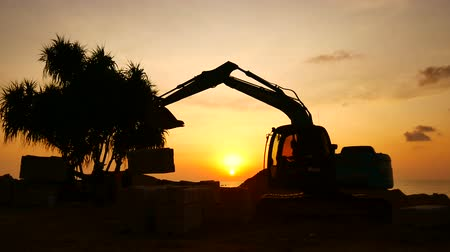 экскаватор : Construction Video At construction site The silhouette excavator is digging ground and lifting a large mortar with engineering and construction workers to help with colorful sunset Стоковые видеозаписи
