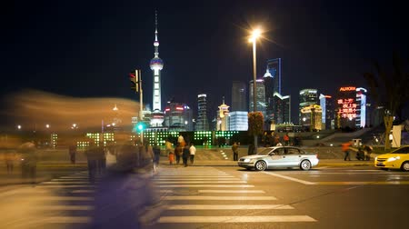 cinematography : people crossing busy road in front of the new pudong skyline illuminated