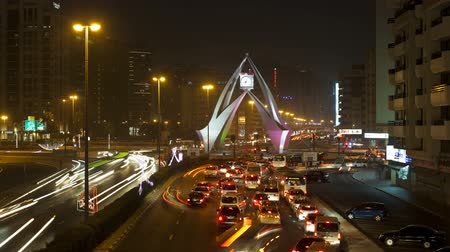 The busy clock tower roundabout illuminated at night Dubai middle East UAE