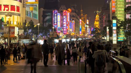Time lapse wide shot of pedestrians walking past stores on Nanjing road at