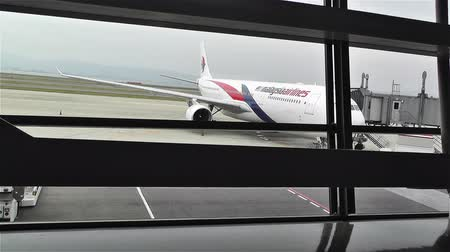 departure : Looking through Window Frames to Malaysia Airline Plane, Surreal Perspective Stock Footage