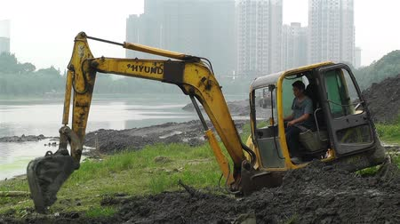экскаватор : Riverbank construction work in Sichuan Chengdu Jintang in China - Excavators digger and shovel dirt and soil on a river shoreline