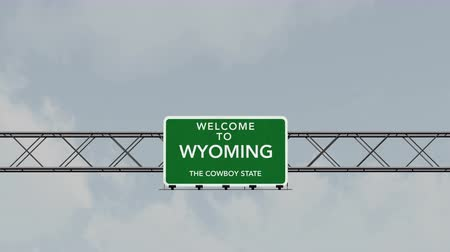 jel : 4K Passing under Welcome to Wyoming State USA Interstate Highway Sign with Matte Photo Realistic 3D Animation Stock mozgókép