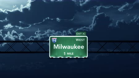 освещенный : 4K Passing under Milwaukee USA Interstate Highway Sign at Night with Matte Photo Realistic 3D Animation Стоковые видеозаписи