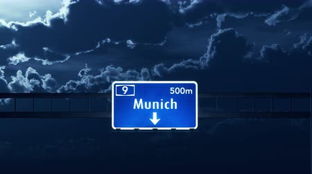 münchen : 4K Passing under Munich Germany Highway Road Sign at Night Photo Realistic 3D Animation with Matte 4K 4096x2304 ultra high definition Stock mozgókép