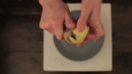 Peeled potatoes with the peel and knife on a wooden table
