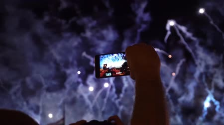 kayıt : man recording Fireworks with mobile phone at a special event