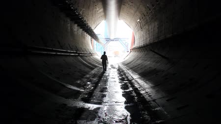 ásta : A man walks through a tunnel.