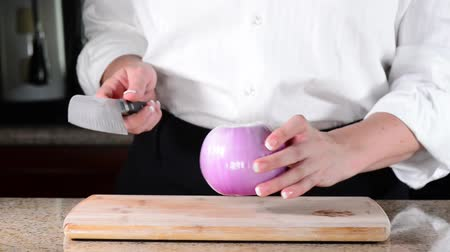 descamação : Chef cutting red onion on wooden cutting board Stock Footage