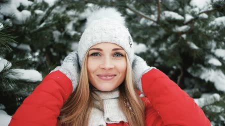 шляпа : Blonde woman taking part in winter photo shoot near fir tree Стоковые видеозаписи