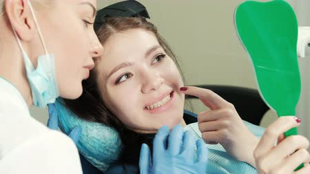 беление : Healthy white woman teeth and dentist mouth mirror closeup. Dental hygiene, oral care concept. Examination at dentistry with dental tools. Tooth whitening of brown-haired client with sunglasses sitting on armchair looking at glass, explaining order to doc Стоковые видеозаписи