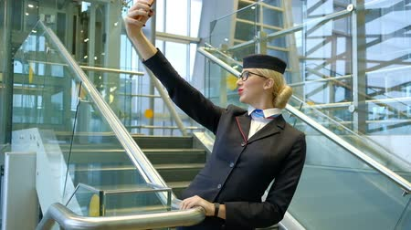 crew : Blonde stewardess standing on stairs making selfie on smartphone. Young air hostess waits before flight entertaining making photos on phone. Fair-haired female looking at telephone, smiling, posing, shows tongue stands inside airport. Blond lady in black
