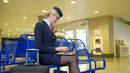 cancelado : Blonde stewardess sitting in departure hall chatting on laptop in airport. Young air hostess waits before flight, typing on keyboard indoors. Fair-haired spend time smiling, chat with friends on computer. Blond female in black uniform jacket white blouse,
