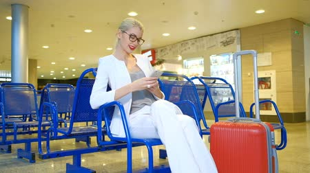 kalkış : Woman in a white suit sitting in the waiting room with the phone. Blonde with glasses and red lipstick writing on the smart phone and smiling. She sits on a blue chair in the hall for passengers and write sms, standing next to a large orange suitcase with Stok Video
