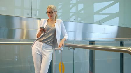 pólos : Slow shooting of woman chatting on phone in departure hall. blond long-haired young attractive female chats on telephone, smiles, laughs, looks on smartphone. Beautiful passenger in white jacket, pants, grey blouse, black spectacles typing on telephone, p Stock Footage