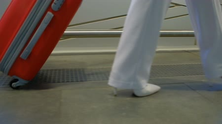 red shoes : Big red suitcase to roll on the arm of a woman in white shoes. Lady dressed in niveous pantsuit, not hastily sweeping the floor with a metal fenced and dragging luggage. Bag has a little black wheels on one side and gray handle for lifting. A long journey