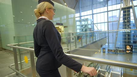 attendant : Blonde stewardess standing in waiting room with suitcase in airport. Young air hostess waits before flight indoors, looks downstairs. Fair-haired female in black uniform jacket white blouse, tissue, glasses bright makeup expects fly on plane. Young fashio