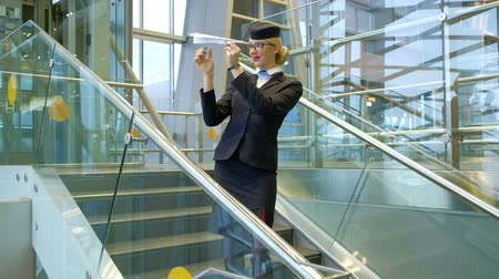 attendant : Blonde stewardess standing on stairs making toy paper plane in hall. Young airhostess waits before flight entertaining makes planes, runs up in air at airport. Fair-haired female looking at camera, smiling, posing, shows stands inside waiting room indoors