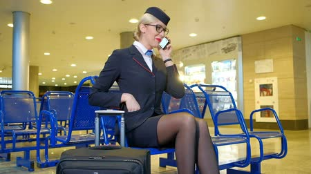 attendant : Blonde stewardess chatting on phone in departure hall. blond elegant young attractive female chats on telephone, smiles, laughs, sits on blue seats. Beautiful female in black uniform jacket white blouse, tissue, glasses bright makeup preparing for flight, Stock Footage
