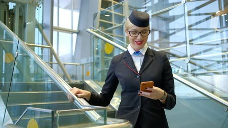 attendant : Stewardess with glasses reading a message on your phone and smiling. At the airport is on the stairs woman in flight attendants uniform and white shirt, holding a brown telephone and leafs through the screen. Tie with a blue stripe on the collar fastened.
