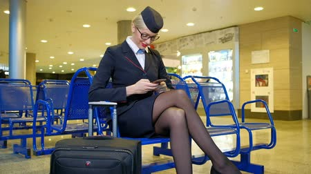 cancelado : At the airport sits stewardess with luggage and holding smartphone. Young woman in a dark uniform in the waiting room waiting for departure of his plane. Her suitcase in black with an elongated handle is near the blue seats. Feet dressed in black transpar Vídeos
