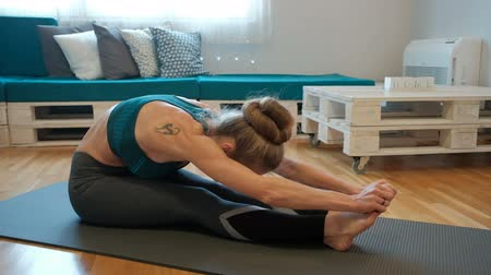 přidání : Woman doing stretching muscles while sitting on a mat near the sofa. The house has a slim athlete leaned forward, his hands holding the heel and extends the body. She is dressed in tight trousers and a green top, in addition to her shoulder tattoo of a ca