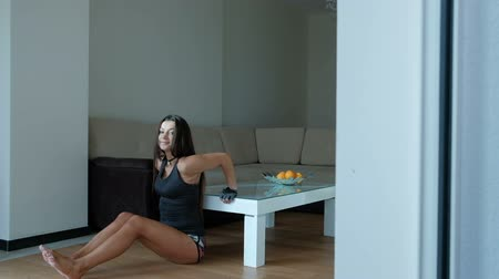 sıkmak : In the apartment woman performs push-ups on the table behind. At home young sexy lady with long black hair alone does sports exercises to train the triceps by flexion and extension arms. Additionally tighten the pectoral and deltoid muscles. Back moves al