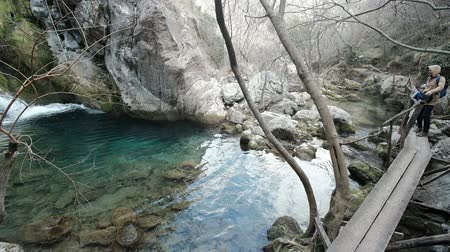 rampouch : Man with boy admire pond with waterfall in mountain in winter. Picturesque landscape based on pure water, it fall from top of hill, flow among stones, partly covered with snow. Aqua is so clean and transparent, as all bottom is seen. Trees in frost comple