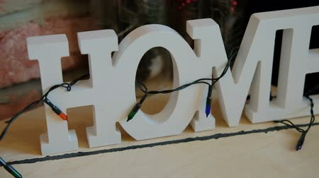 глыба : Big white plastic 3d inscription with word home decorated with bulbs. On wooden table or desk stand four letters as they become text. Camera go from letter e to h, they all are uppercase, same height. Decoration of this house design is garland with lights Стоковые видеозаписи
