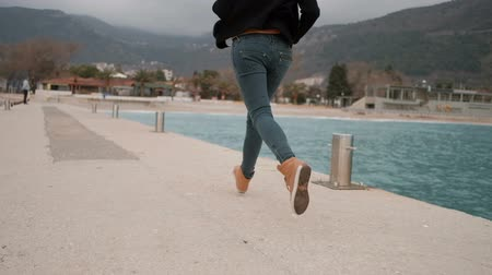 human foot : Woman running along pier, embankment near lake. View from back. Video start from womans foot in orange boots with lace same color. She run along concrete surface, on which sometimes words in English, metal column streak. Then camera raise, female dressed