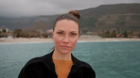 enviroment : close shot of woman face on shore of lake, looking into camera. Attractive female with brown hair walking on sea mountains on background. Closeup shooting nice lady in black jacket, red sweater, natural makeup walks on beach, enjoying nature, dreams, watc