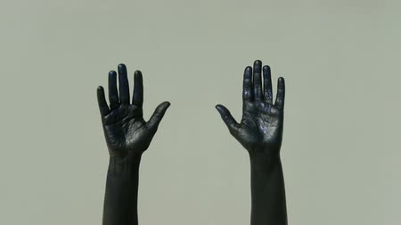 until : Actor mime with black hands shows gesture goodbye on a gray background. Palms in shiny paint in blue tint flex and unbend fingers slowly. The limbs are stretched and pantomime moves. When parting for an indefinite period of time, a person shows by gesture