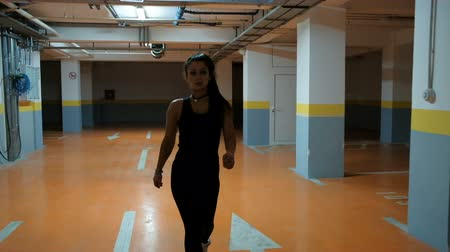poník : Professional sportswoman goes In parking lot slow shooting from front. Cheerful fit brunette lady with brown long hair, pony tail perfect body in black t-shirt, pants walks to sport working out on street, having rest between trainings. Slow-motion of beau