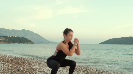 quadriceps : Young slim woman in training suit do exercises on beach near ocean. Beautiful brunette with ponytail in black skinny sportswear with red, pink, yellow, green, blue stripes on back, grey snickers, bracelets on both hands, choker warming up at sea shore. Sh