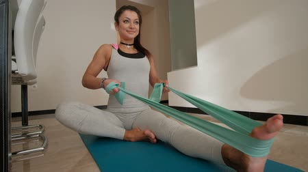 direnç : Sporty woman doing exercises with tight band fitness at home indoors. Attractive athlete female with black long hair pony tail pulling on bands to chest, harnes clinging on leg, shakes arms muscles on mat carpet. Lunge on right foot, girth with turquoise