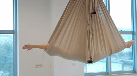 zámotek : In a closed hammock for yoga in the air, a woman lies and rocks. She meditates in the unfolded canvas, which is attached to the ceiling. Beige matter in the form of a cocoon keeps the human body. The limbs are straightened to the full length. On the side  Dostupné videozáznamy