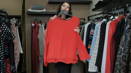 vállfa : Brunette woman choosing sweater from rack with hangers inside room. Attractive lady with long black wavy hair looks to dresses, decides what to wear, takes red sweater, trying on, smiles, goes out. Fashionable female in dark classic dress, with bright mak Stock mozgókép