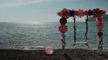 оставлять : At sunset at the shore stand a swing with decorations and a ball. At sunset on the beach in sunny weather there is a white design that decorates with large bright flowers at the top. Nearby is a pink ball. The waves sway softly from the wind. The sun refl