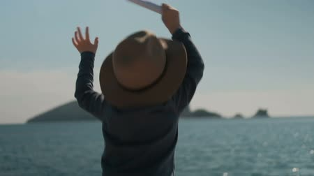 urgência : Small boy actively waving hands, calling his parents from sea. View back of child 6 years old, in dark blue sweatshirt with long sleeves, in hat with small brim and twisted leaf of paper in arm, jumps up and swings his hands quickly, trying get attention