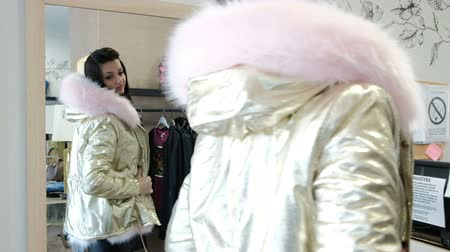 ceket : brunette woman trying on jacket in dressing room clothing store. Fashionable female with straight black hair, bright make-up twisting in front of mirror in boutique. Nice beautiful lady dressed in golden-colored outer garment with pink fur, puts on hood,